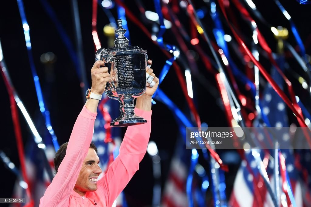 TOPSHOT - Spain's Rafael Nadal holds up his winning trophy after defeating South Africa's Kevin Anderson during their 2017 US Open Men's Singles final match at the USTA Billie Jean King National Tennis Center in New York on September 10, 2017. Rafael Nadal raced to a third US Open title and 16th Grand Slam crown on Sunday with a 6-3, 6-3, 6-4 rout of South African giant Kevin Anderson. / AFP PHOTO / Jewel SAMAD