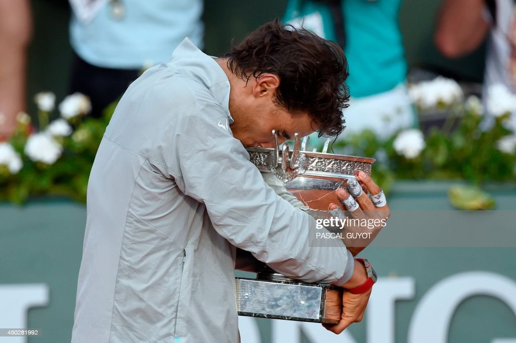 Spain's Rafael Nadal kissess the Musketeers trophy after winning the French tennis Open men's final match against Serbia's Novak Djokovic at the Roland Garros stadium in Paris on June 8, 2014. AFP PHOTO / PASCAL GUYOT / AFP PHOTO / Pascal GUYOT
