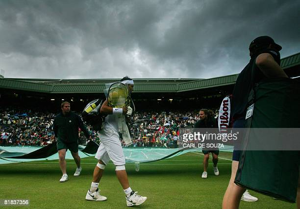 Spain's Rafael Nadal leaves the court due to the rain during the final tennis match of the 2008 Wimbledon championships against Switzerland's Roger...