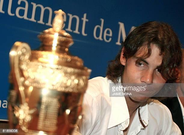 Spain's Rafael Nadal looks at his Wimbledon trophy at the Manacor's town hall, Mallorca, Balearics Islands on July 08, 2008. Rafael Nadal dethroned...