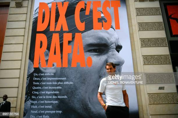Spain's Rafael Nadal poses by a poster reading 'Ten It's Rafa' refering to his tenth win at the French Tennis Open during a promotional event at the...