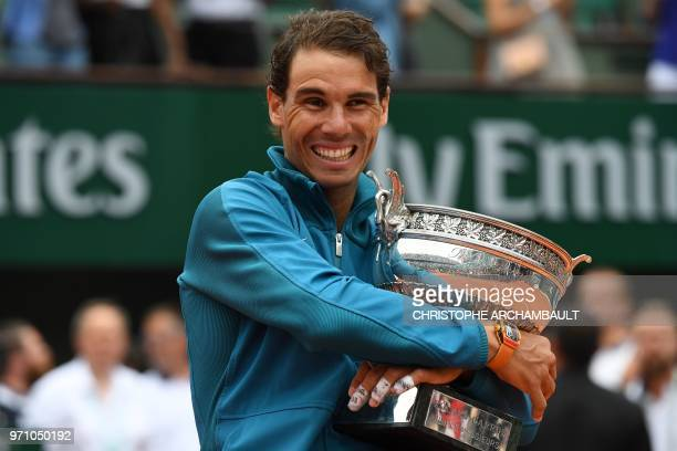 Spain's Rafael Nadal poses with the Mousquetaires Cup after his victory in the men's singles final match against Austria's Dominic Thiem on day...