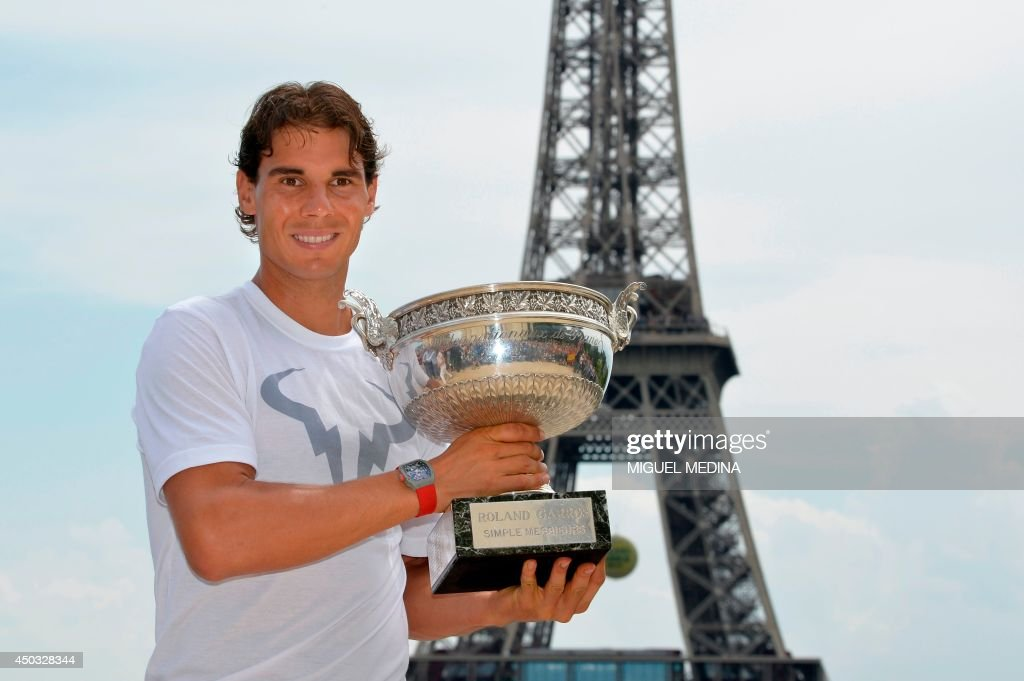 Spain's Rafael Nadal poses with the Musketeers trophy on June 9, 2014 in Paris, a day after winning the French tennis Open men's final match at the Roland Garros stadium. The 28-year-old Spaniard stormed to a ninth French Open triumph on June 8 with a 3-6, 7-5, 6-2, 6-4 win over Novak Djokovic which also secured his 14th Grand Slam crown. AFP PHOTO / MIGUEL MEDINA / AFP PHOTO / Miguel MEDINA