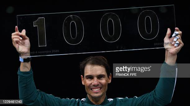 Spain's Rafael Nadal poses with the trophy of his one thousandth victory of the ATP at the end of his men's singles second round tennis match against...