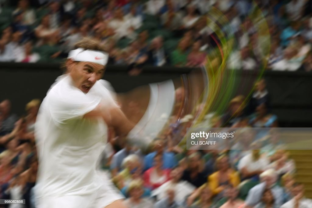 Spain's Rafael Nadal returns against Serbia's Novak Djokovic during their men's singles semi-final match on the eleventh day of the 2018 Wimbledon Championships at The All England Lawn Tennis Club in Wimbledon, southwest London, on July 13, 2018. (Photo by Oli SCARFF / AFP) / RESTRICTED