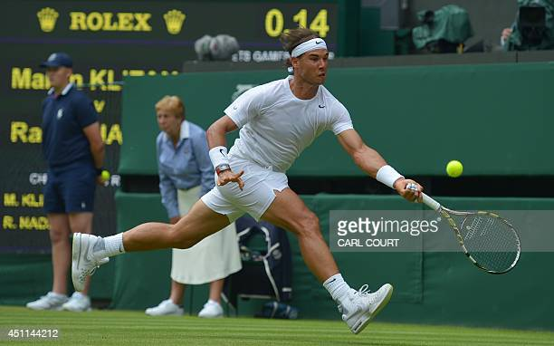 Spain's Rafael Nadal returns against Slovakia's Martin Klizan during their men's singles first round match on day two of the 2014 Wimbledon...