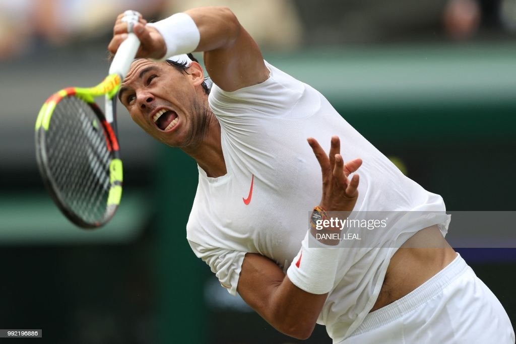 TOPSHOT - Spain's Rafael Nadal serves to Kazakhstan's Mikhail Kukushkin in their men's singles second round match on the fourth day of the 2018 Wimbledon Championships at The All England Lawn Tennis Club in Wimbledon, southwest London, on July 5, 2018. (Photo by Daniel LEAL-OLIVAS / AFP) / RESTRICTED