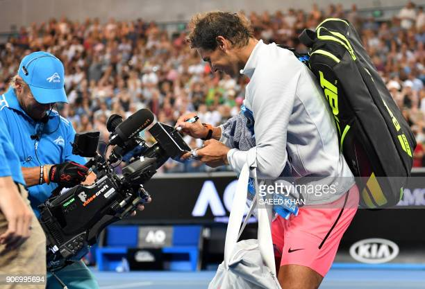 Spain's Rafael Nadal signs an autograph on a cameraman's screen after beating Bosnia's Damir Dzumhur in their men's singles third round match on day...