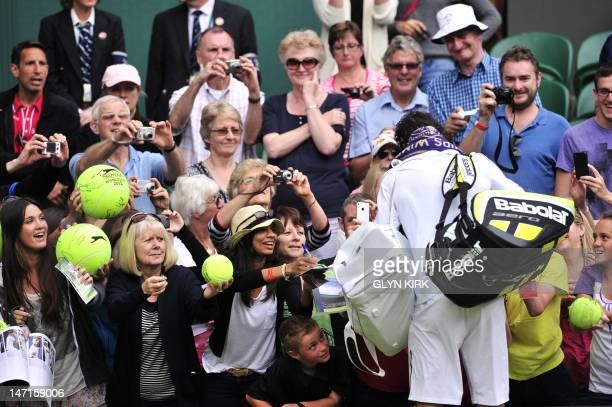Spain's Rafael Nadal signs autographs for fans after his first round men's singles victory over Brazil's Thomaz Bellucci on the second day of the...