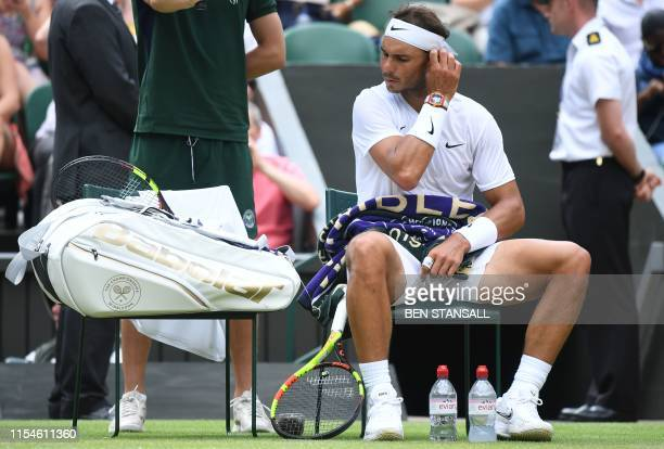 Spain's Rafael Nadal sits during his men's singles fourth round match against Portugal's Joao Sousa on the seventh day of the 2019 Wimbledon...