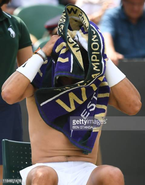 Spain's Rafael Nadal uses a towel as he plays Portugal's Joao Sousa during their men's singles fourth round match on the seventh day of the 2019...