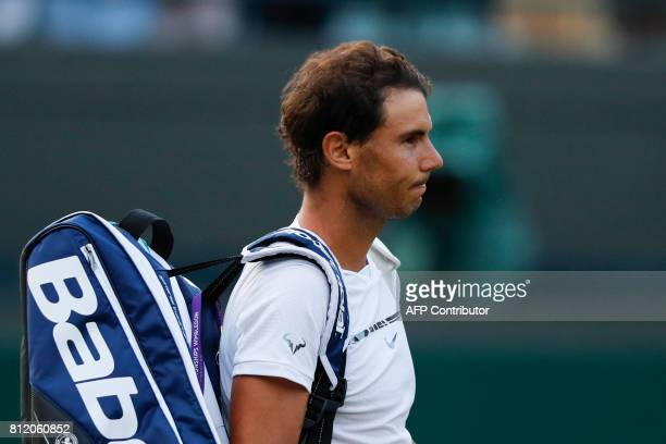 TOPSHOT Spain's Rafael Nadal waits for Luxembourg's Gilles Muller to collect his bag so that they can leave the court together after Muller won their...