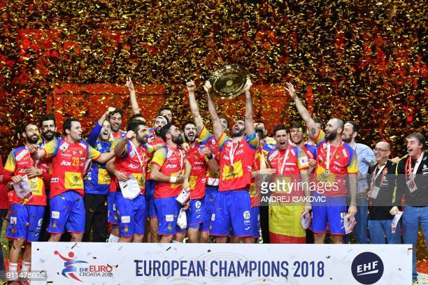 TOPSHOT Spain's Raul Entrerrios holds the EHF European Handball Championship trophy as Spain's players celebrate during the podium ceremony after...