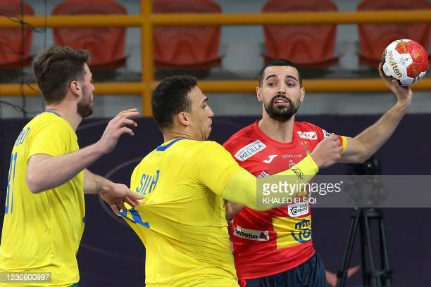 Spain's right winger Ferran Sole is challenged by Brazil's centre back Joao Silva during the 2021 World Men's Handball Championship between Group B...