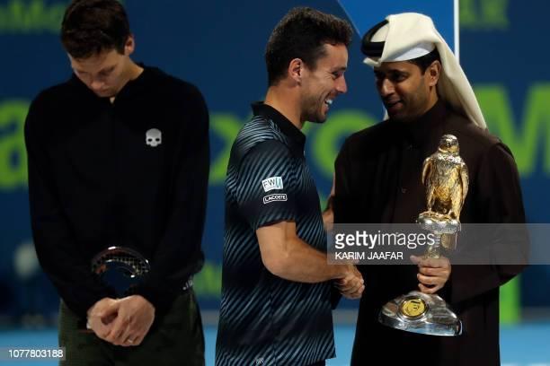 Spain's Roberto Bautista Agut receives the trophy from Asian tennis federation president Nasser al-Khelaifi after winning against Czech Republic's...