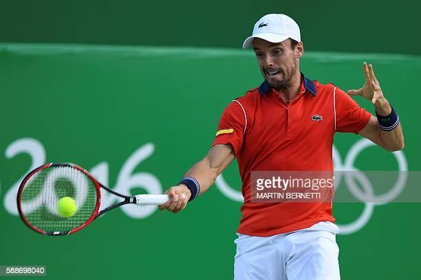 Spain's Roberto Bautista Agut returns the ball to Argentina's Juan Martin Del Potro during their men's singles quarter-final tennis match at the...