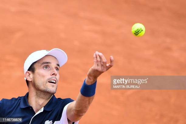 Spain's Roberto Bautista Agut serves the ball to Steve Johnson of the US during their men's singles first round match on day three of The Roland...