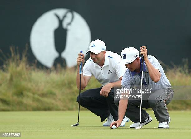 Spain's Sergio Garcia and US golfer Rickie Fowler line up their putts on the 3rd green during the third round on day three of the 2014 British Open...