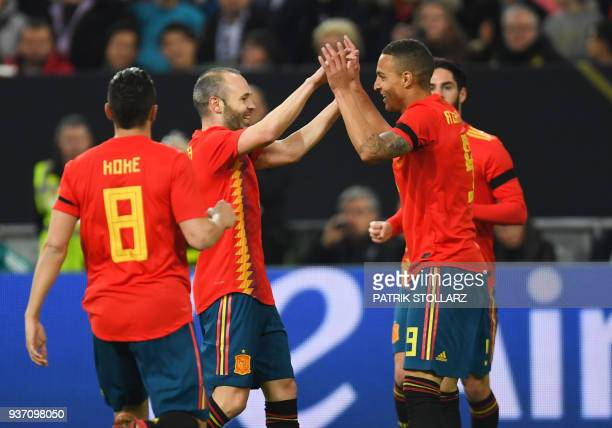 Spain's Spain's forward Rodrigo is congratulated by Spain's midfielder Andres Iniesta and Spain's midfielder Koke after scoring the 01 during the...