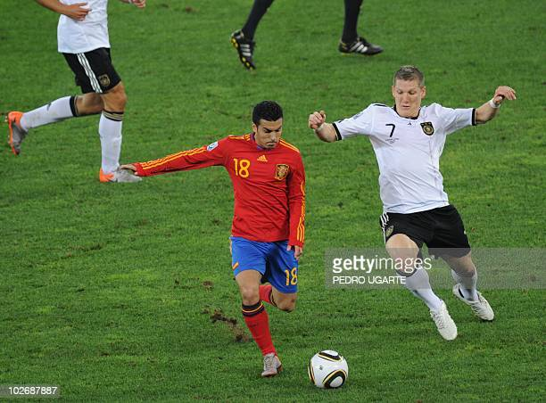 Spain's striker Pedro fights for the ball with Germany's midfielder Bastian Schweinsteiger during the 2010 World Cup semifinal match Germany vs Spain...