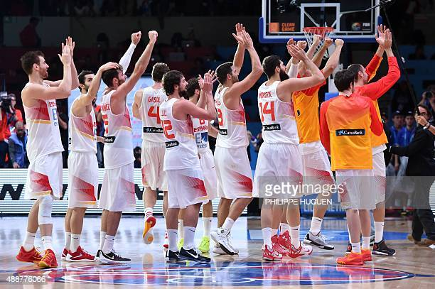 Spain's teammates acknowledge their supporters as they celebrate after defeating France in the semifinal basketball match between Spain and France at...