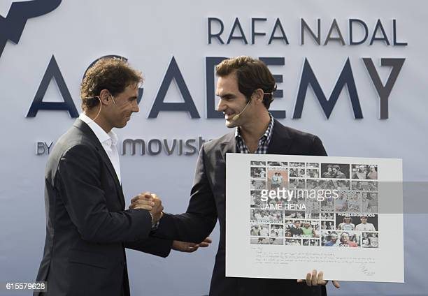 Spain's tennis player Rafael Nadal hands a poster with pictures taken during his matches with Swiss's player tennis Roger Federer to Federer at the...