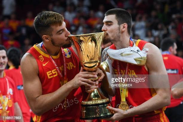 Spain's Willy Hernangomez and Juan Hernangomez kiss their winning trophy at the end of the Basketball World Cup final game between Argentina and...