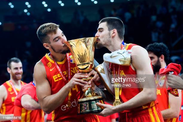 TOPSHOT Spain's Willy Hernangomez and Juan Hernangomez kiss their winning trophy at the end of the Basketball World Cup final game between Argentina...