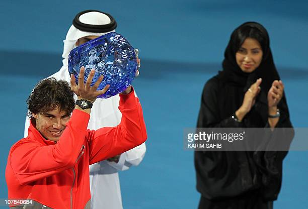 Spain's world number one Rafael Nadal poses with the trophy in his hand after beating Swiss tennis icon Roger Federer in the Mubadala World Tennis...