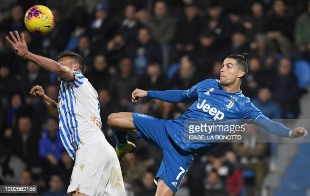 Spal's Polish defender Thiago Cionek and Juventus' Portuguese forward Cristiano Ronaldo go for the ball during the Italian Serie A football match...