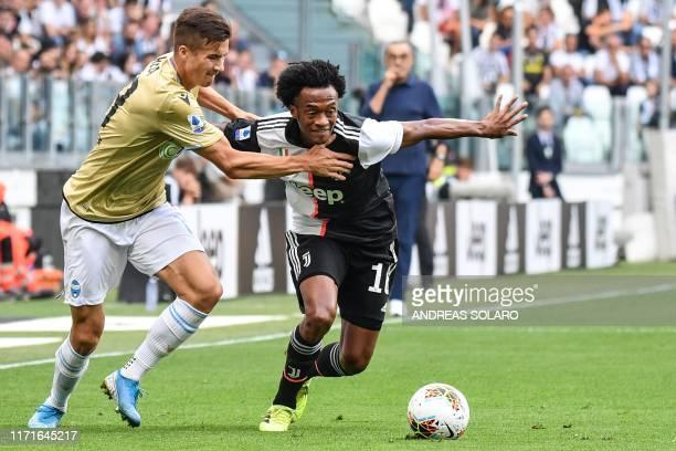 Spal's Polish midfielder Arkadiusz Reca holds off Juventus' Colombian midfielder Juan Cuadrado during the Italian Serie A football match Juventus vs...