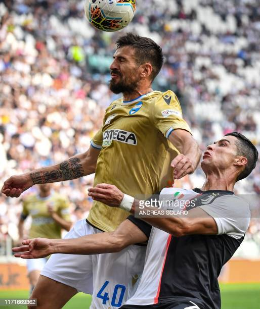 Spal's Serbian defender Nenad Tomovic and Juventus' Portuguese forward Cristiano Ronaldo go for a header during the Italian Serie A football match...