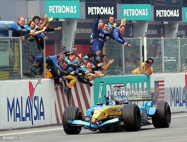 Spaniard Fernando Alonso of Renault celebrates with his crew as he passes the finish line at the Formula One Malaysian Grand Prix 20 March 2005 at...