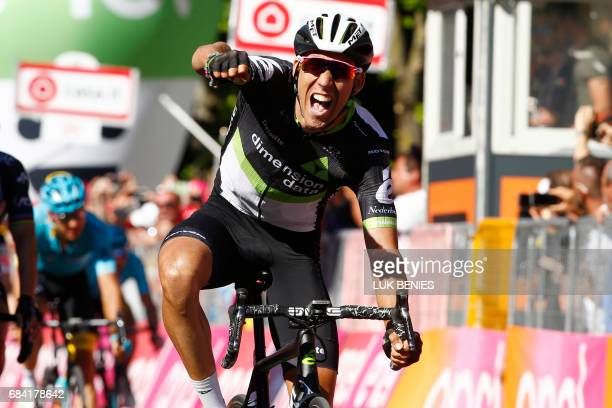 TOPSHOT Spaniard Omar Fraile of team Dimension Data celebrates as he crosses the finish line to win the 11th stage of the 100th Giro d'Italia Tour of...