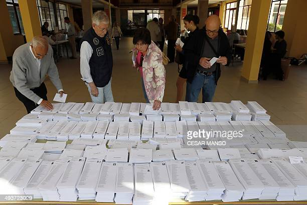 Spaniards pick up ballot papers for the European Parliament elections at a polling station in Madrid on May 25 2014 Some 400 million Europeans are...
