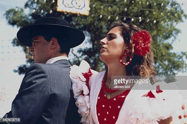 Ein junges Paar hat sich anlässlich der AprilFeria in Sevilla festlich gekleidet Die Frau trägt ein buntes traditionelles Kleid eine rote Blume im...