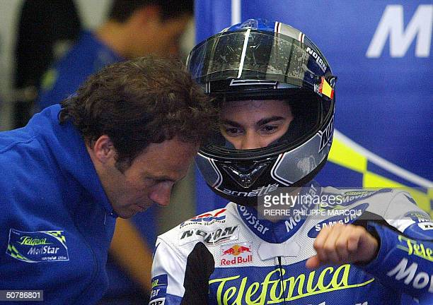 Spanish 250cc rider Dani Pedrosa gestures as he speaks to his coach Alberto Puig during a free practice session in Jerez 30 April 2004 AFP PHOTO/...