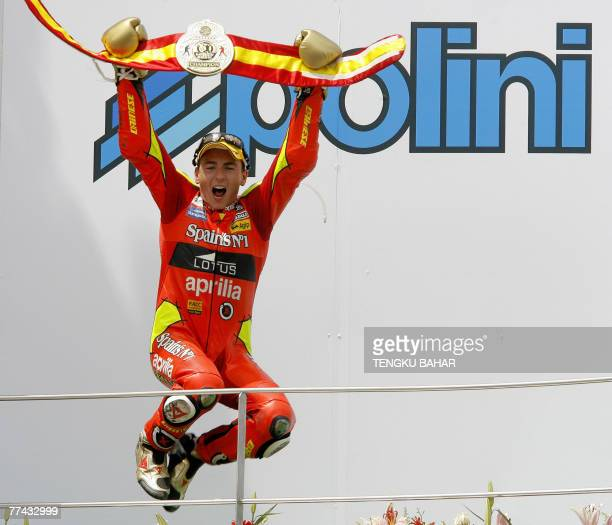 Spanish 250cc rider Jorge Lorenzo wearing gold boxing gloves and a championship belt provided by his teammates jumps in jubilation after cliching the...