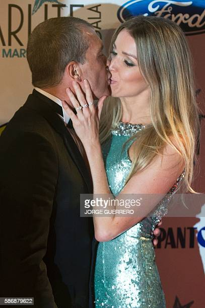 Spanish actor Antonio Banderas kisses his partner Nicole Kimpel at the seventh edition of the Starlite Charity Gala in Marbella on August 6 2016 /...
