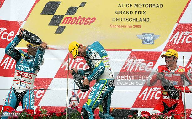 Spanish Aprilia drivers Julian Simon Sergio Gadea and Spanish Derbi driver Jean Olive celebrate with champagne their ranks on the podium after the...