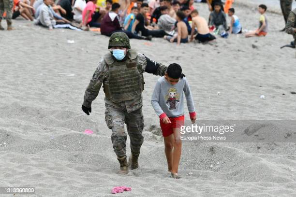Spanish army soldier accompanies a child on a day marked by the hot returns that are being carried out to migrants who have entered Ceuta from...