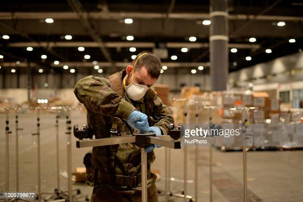 Spanish army soldiers mounting serums holder at the temporary hospital for COVID19 patients located at the Ifema convention and exhibition centre in...