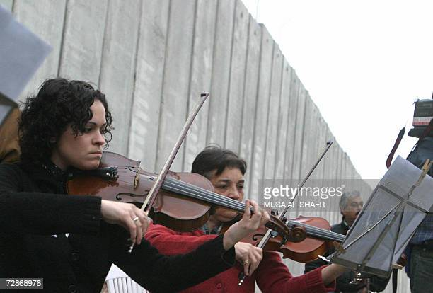 Spanish artist Cristina del Valle conducts an orchestra in front of the controversial separation barrier being built by Israel and said to be illegal...