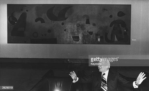 Spanish artist Joan Miro at one of his exhibitions standing in front of his work Original Publication People Disc HN0495