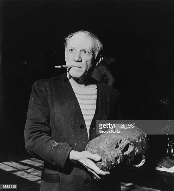 Spanish artist Pablo Picasso holding a piece of sculpture
