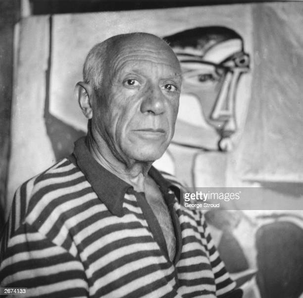 Spanish artist Pablo Picasso in front of one of his paintings at home in Cannes