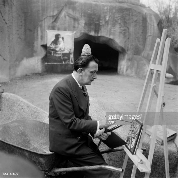 Spanish artist Salvador Dali one of the most popular painters of the 20th century is painting with a bread crust on his head on April 30 1955 in the...