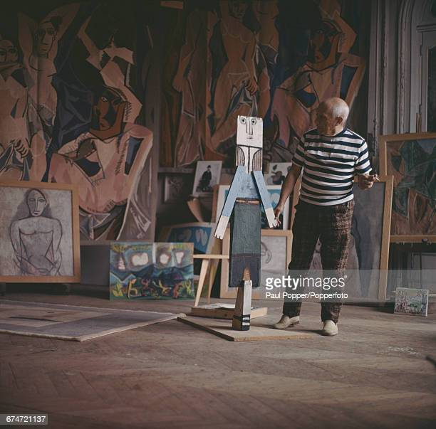 Spanish artist sculptor and painter Pablo Picasso pictured smoking a cigarette as he examines one of his sculptures at his house near Cannes in...