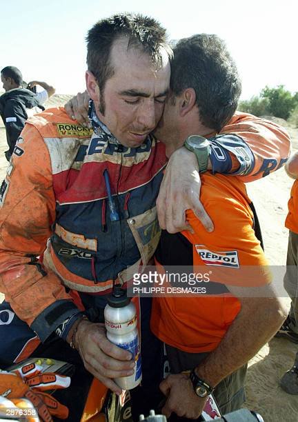 Spanish biker Nani Roma first in the overhall standings is congratulated by his mechanic 17 January 2004 upon his arrival at the end of the 16th...