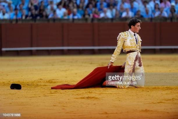 Spanish bullfighter Alfonso Cadaval kneels to receive the bull during a bullfight at the Real Maestranza bullring in Sevilla on September 30 2018